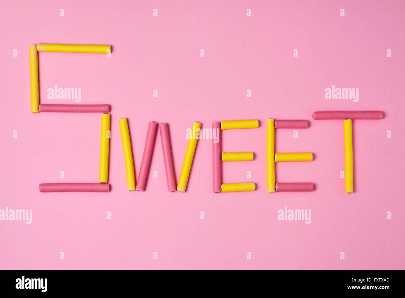 Giallo e rosa marshmallows rivestita formando la parola dolce su un sfondo rosa Immagini Stock