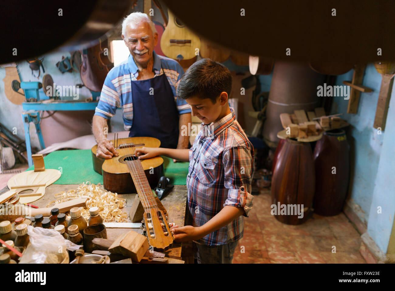 Piccola azienda di famiglia e tradizioni: il nonno vecchio con il nipote in liutaio shop. Il senior artigiano insegna Immagini Stock