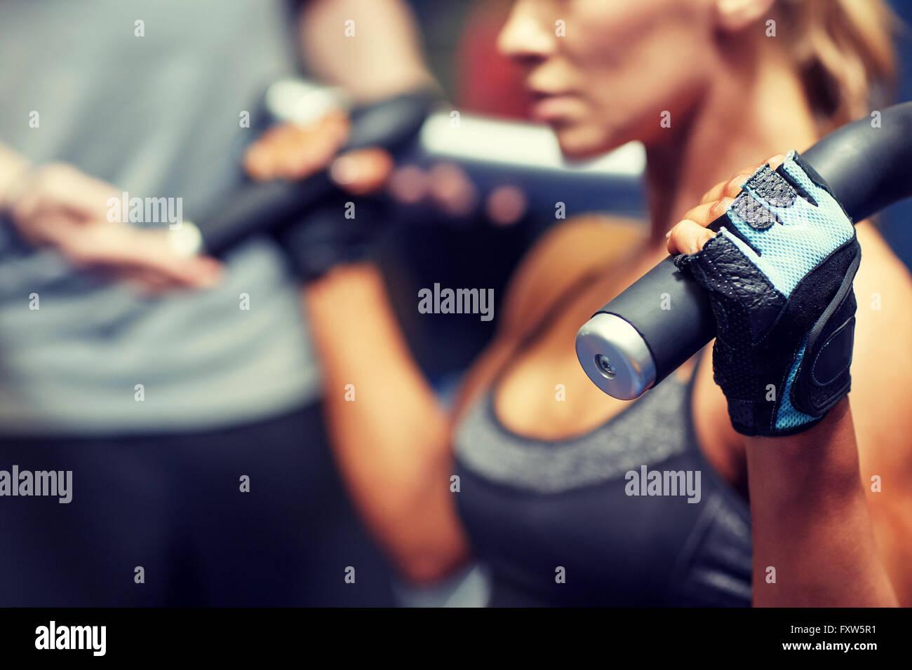 L uomo e la donna i muscoli di flessione sulla macchina palestra Immagini Stock