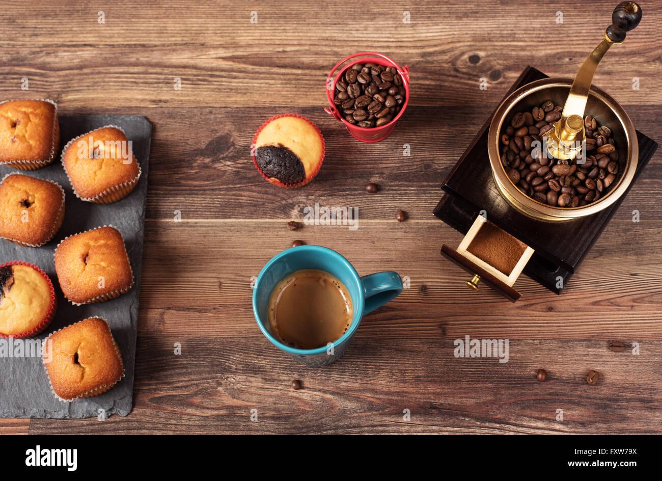 Retrò macinino da caffè, coffee mill tazza da caffè, cioccolato tortina, muffin, i chicchi di caffè. Immagini Stock