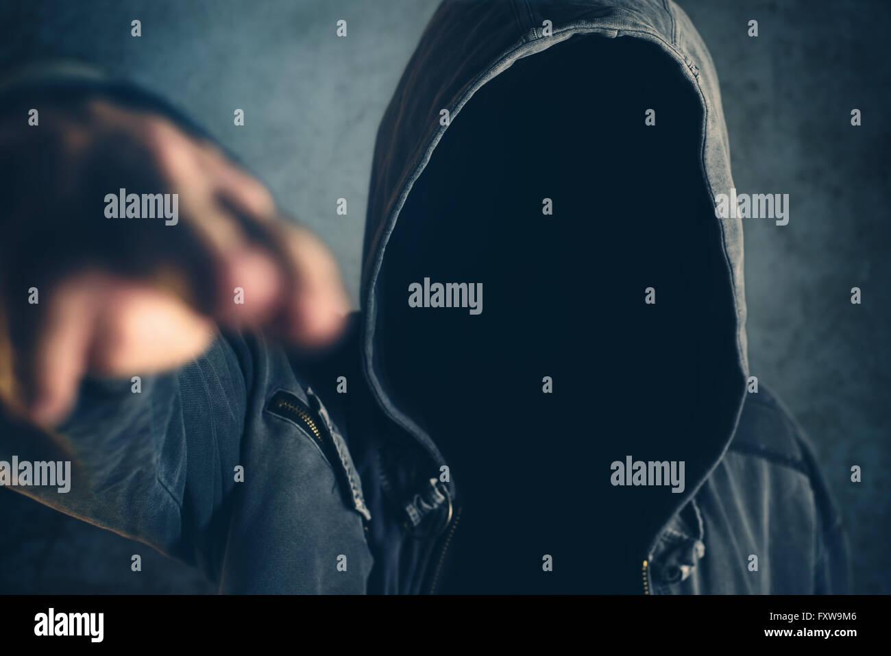 Con cappuccio gesti criminali spari con le dita, spooky gangster persona dita di puntamento al visualizzatore, il Immagini Stock
