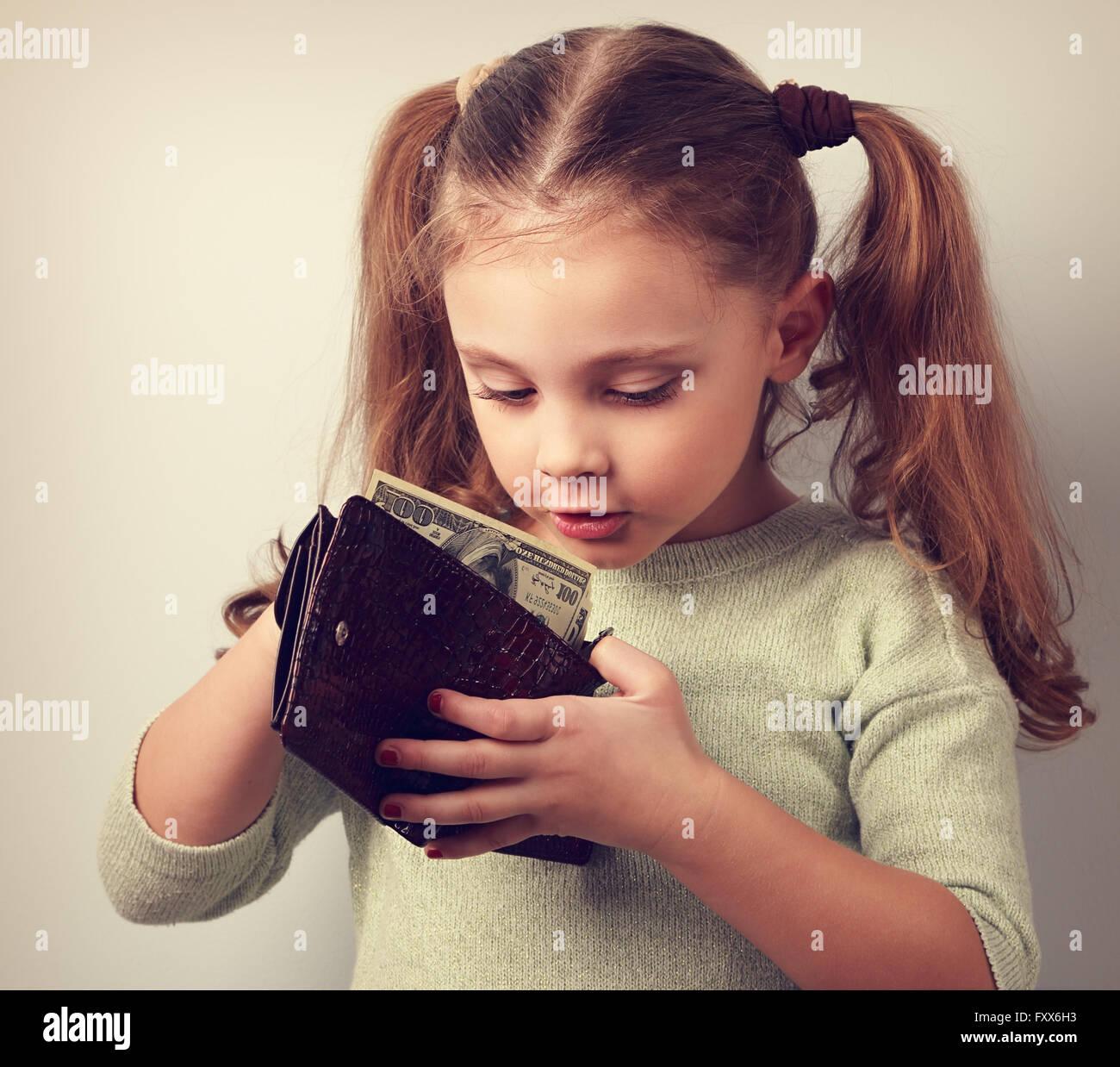 Carino sorprendente piccolo ragazzo cerca ragazza madre in portafoglio e desidera prendere soldi. Tonica closeup Immagini Stock