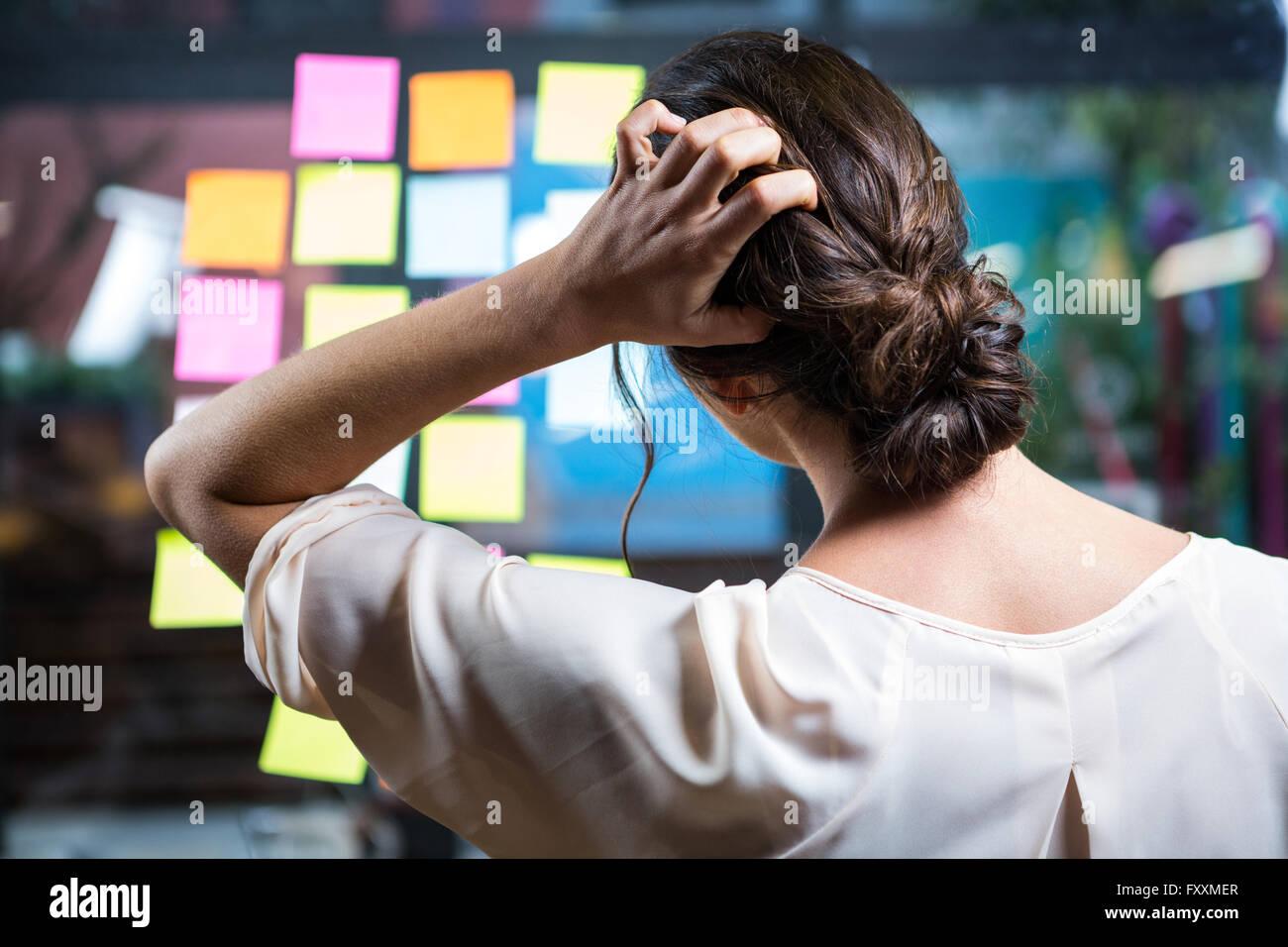 Preoccupato imprenditrice guardando una nota adesiva Immagini Stock