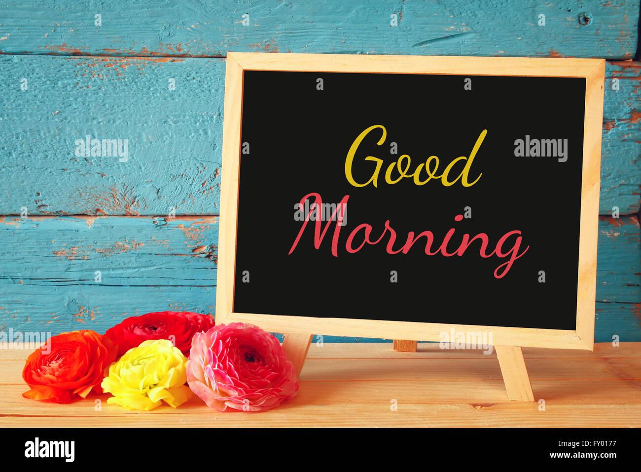 Lavagna con la frase buona mattina scritto su di esso accanto a fiori freschi. Immagini Stock