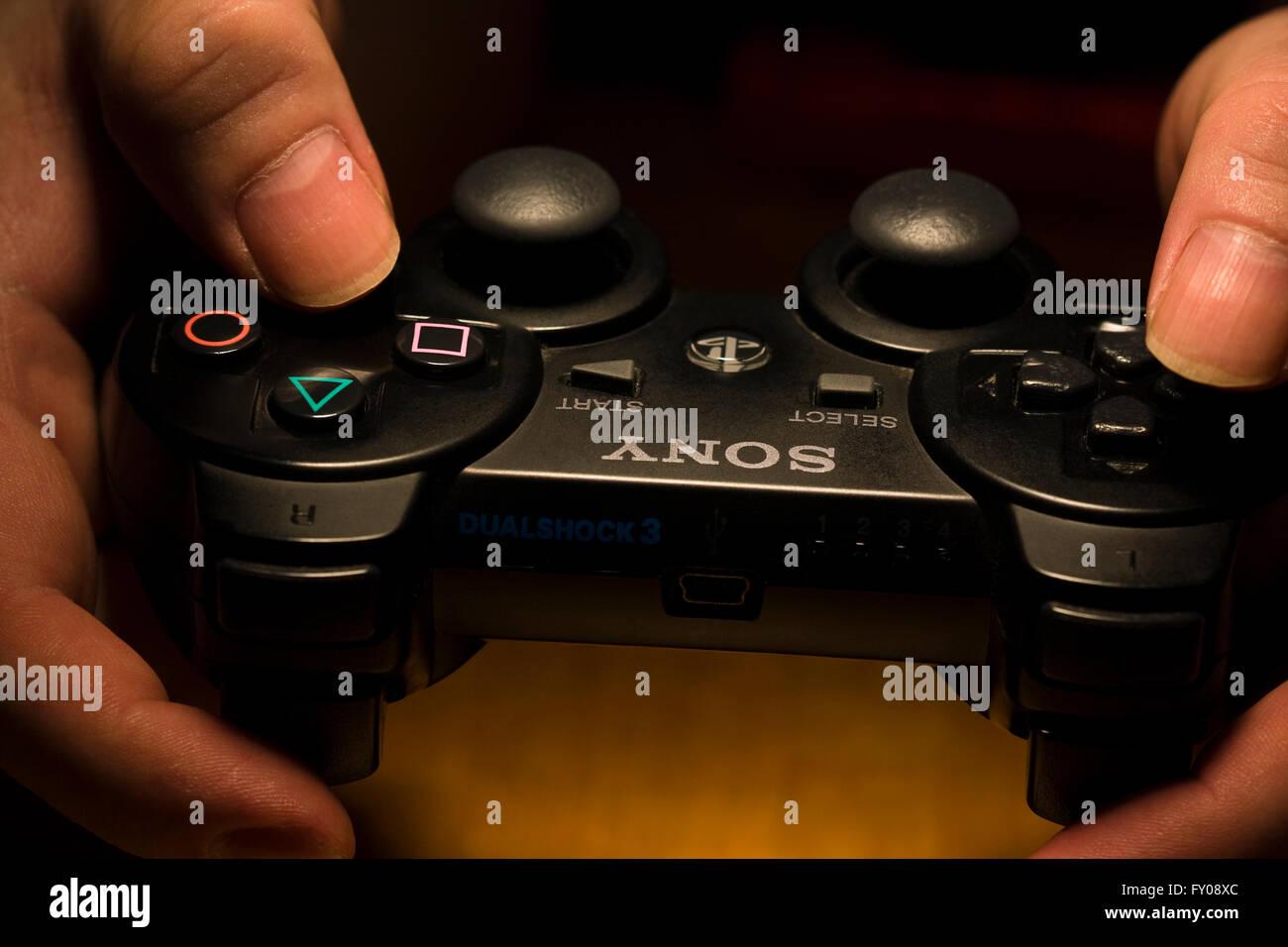 Due mani tenendo un wireless Sony Playstation Dual Shock 3 Controller Immagini Stock