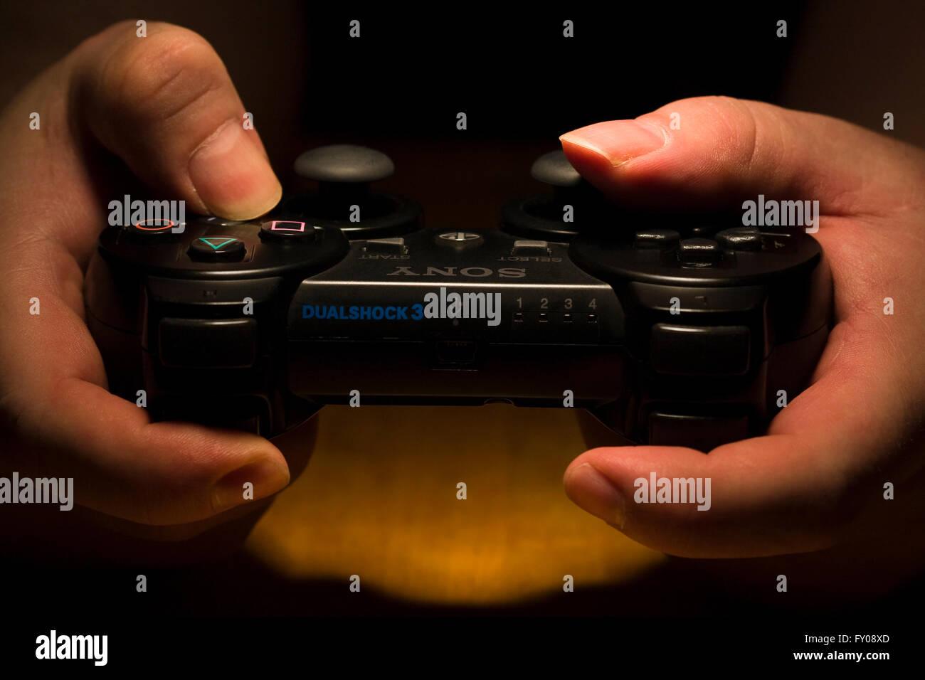 Due mani tenendo un wireless Sony Playstation Dual Shock 3 Controller mentre i pollici sono premendo i pulsanti Immagini Stock