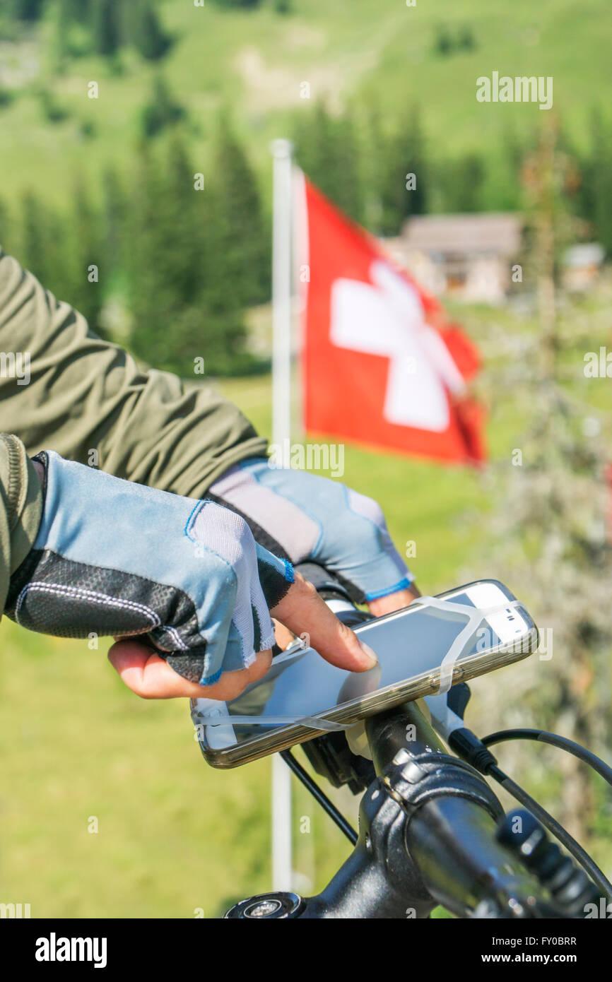 Turismo in bicicletta nelle montagne della svizzera utilizza il suo smart phone per la navigazione Immagini Stock