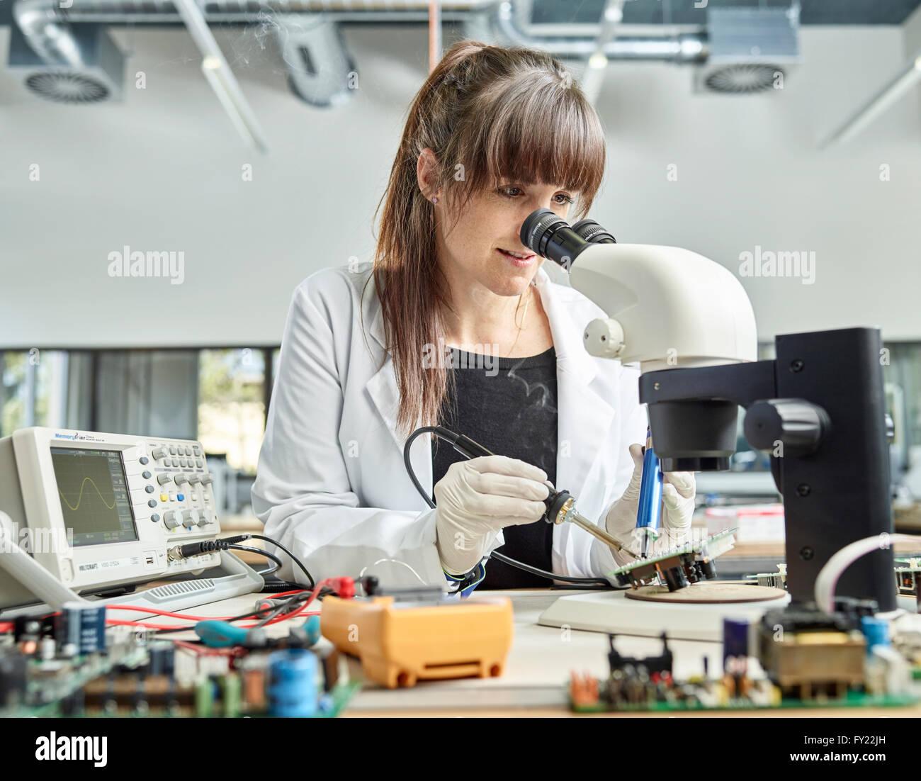 Tecnico femmina, 20-25 anni, con un bianco camice, la saldatura di una scheda di circuito in un laboratorio di elettronica, Foto Stock