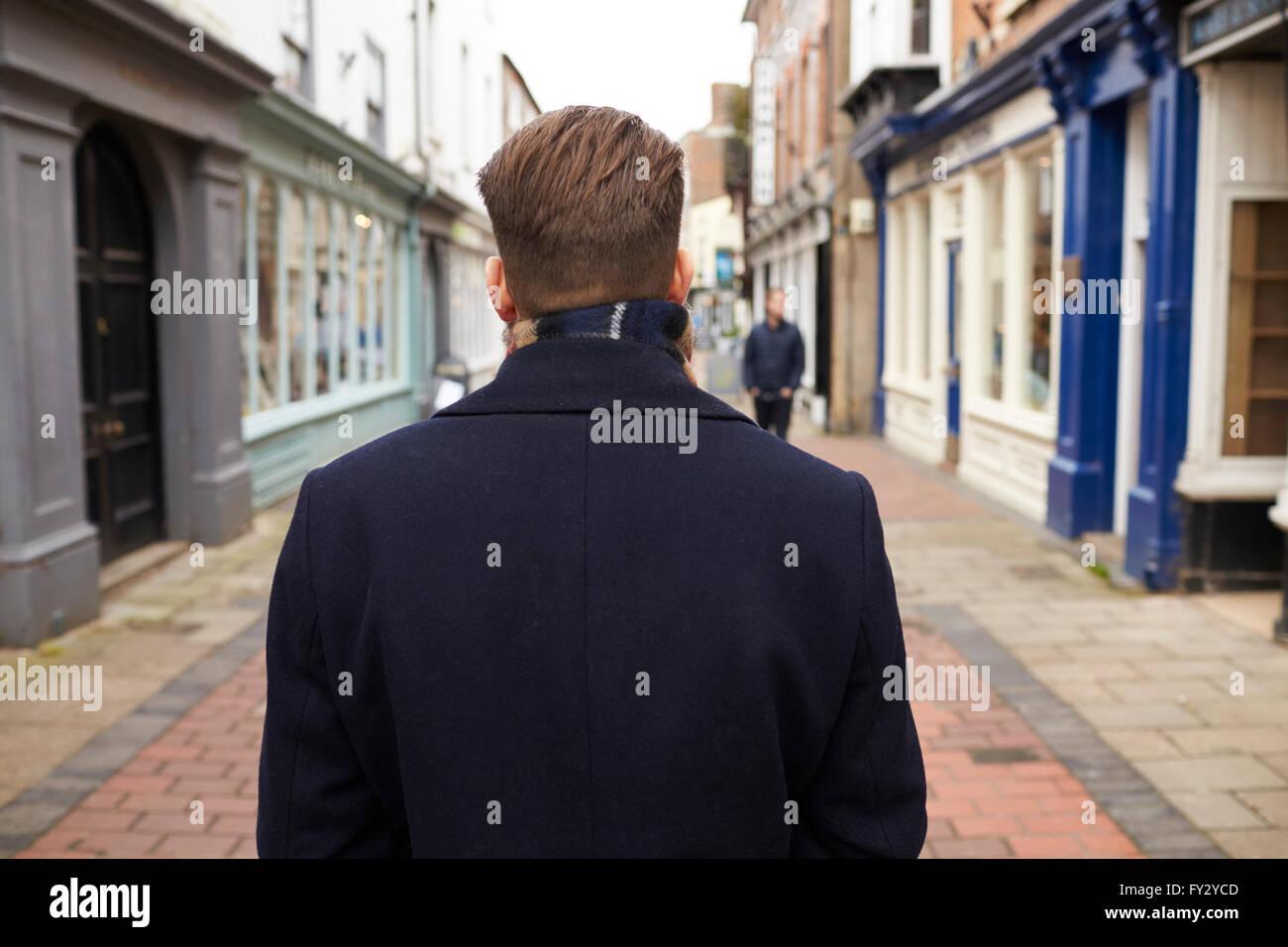 Vista posteriore del giovane di camminare per strada urbana Immagini Stock
