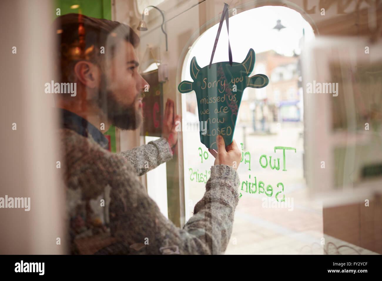 Proprietario maschio del Coffee Shop girando segno aperto Immagini Stock
