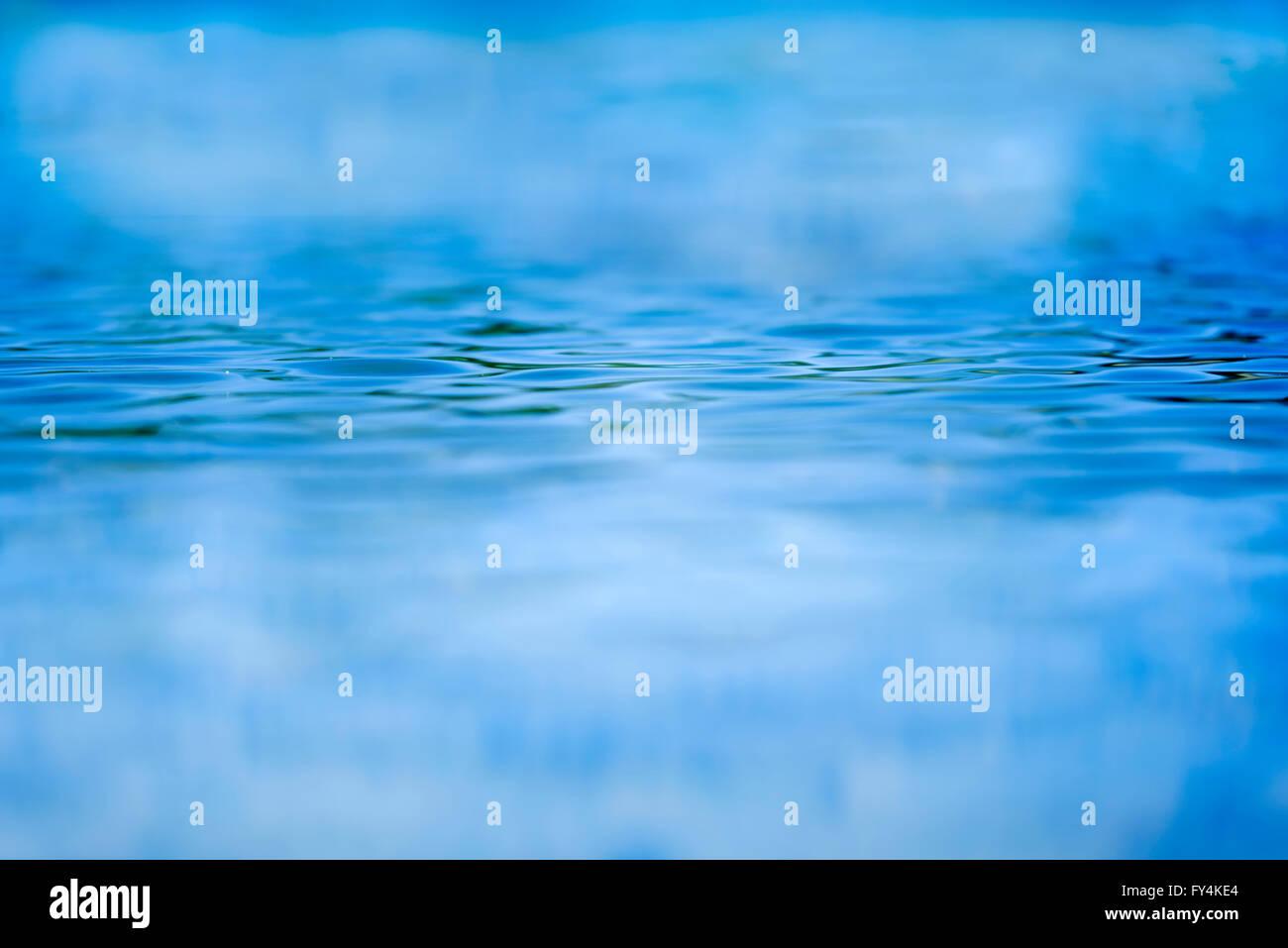 Messa a fuoco poco profonde guardando attraverso l'acqua blu con increspature Immagini Stock