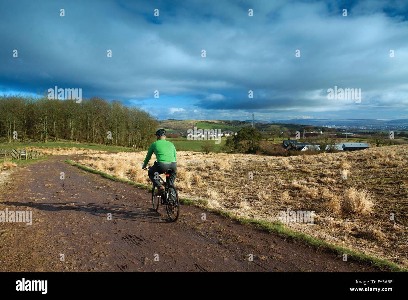 Un ciclista in bicicletta intorno Neilston Pad, Neilston, East Renfrewshire Immagini Stock