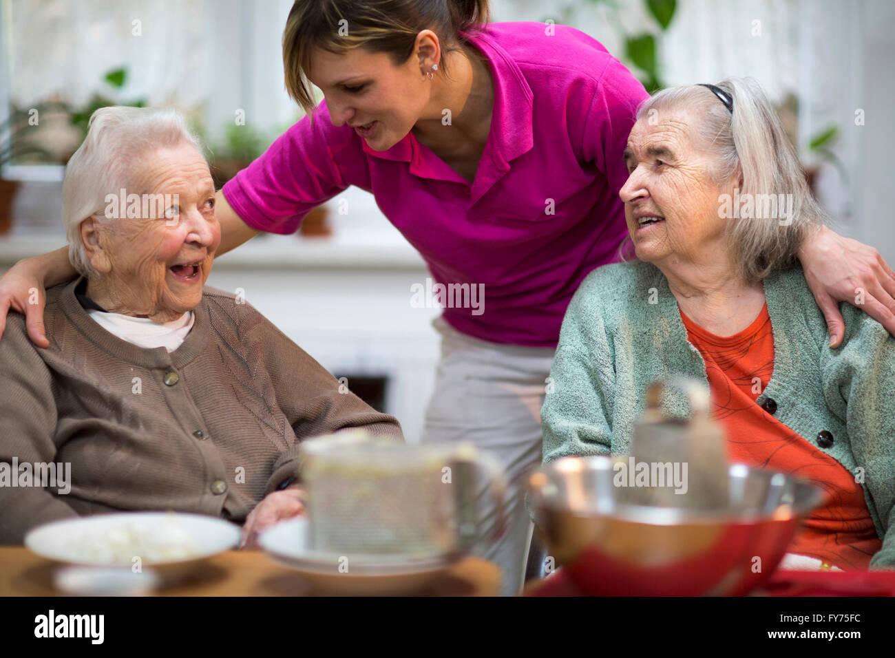 Due donne anziane, 78 anni e 88 anni e un accompagnatore per anziani, 31 anni, attività per il tempo libero Immagini Stock