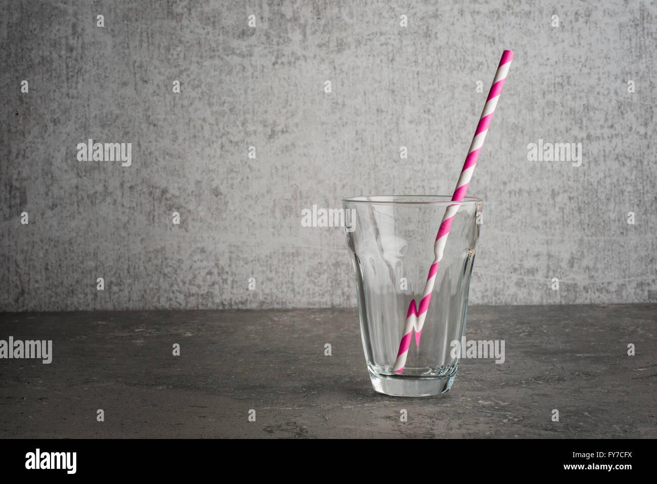 Bicchiere vuoto con cannuccia studio ancora in vita la paglia è a strisce del vetro è st ing su un tavolo Immagini Stock