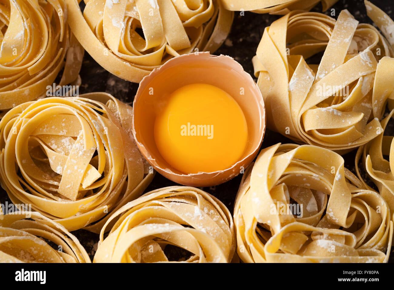 Fettuccine cibo italiano ancora vita rustica laici piatto sfondo nero tagliatelle alfredo tuorlo close up macro Immagini Stock