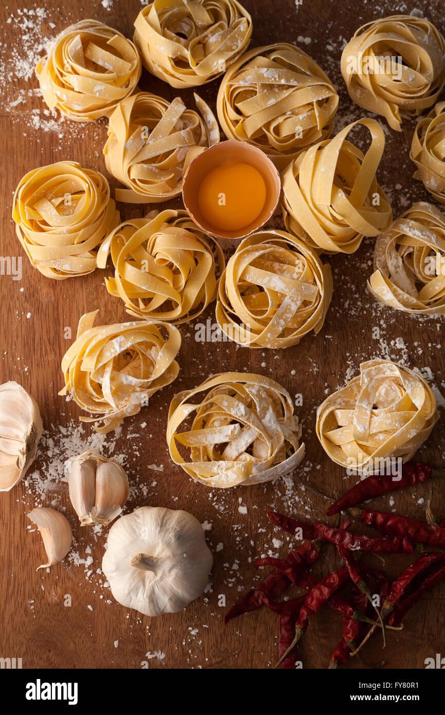 Fettuccine cibo italiano ancora vita rustica laici piatto Sfondo legno tagliatelle alfredo Aglio Peperoncino tuorlo Immagini Stock