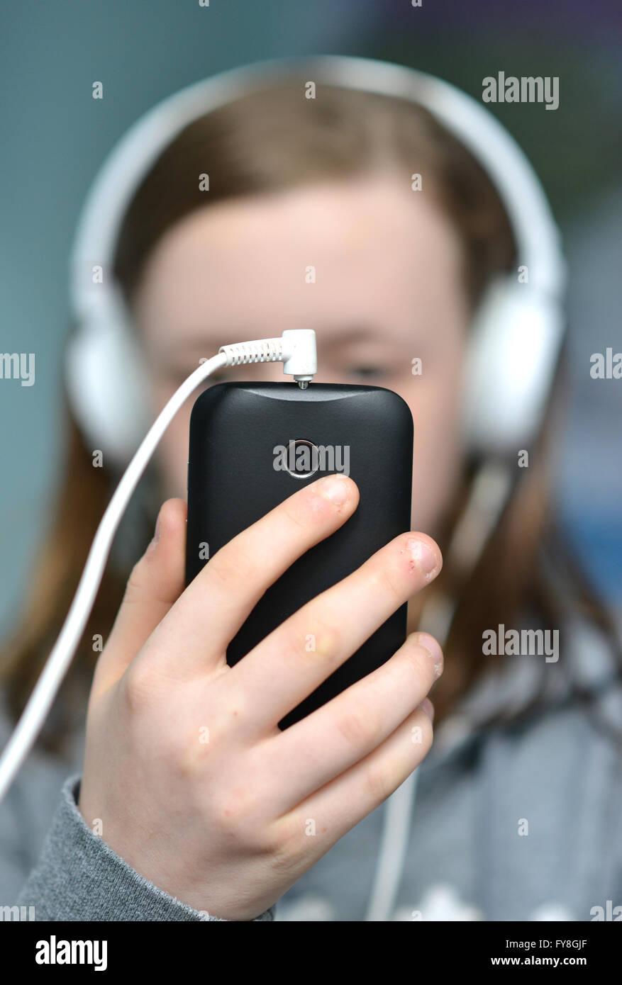 Teen ragazza con mobile (cellulare) telefono e cuffie Immagini Stock