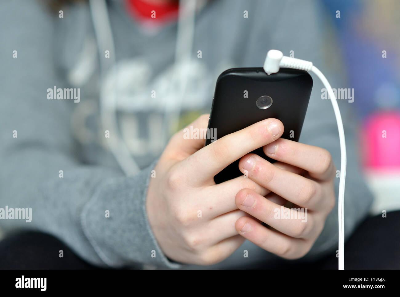 Teen azienda mobile (cellulare) telefono in mani Immagini Stock