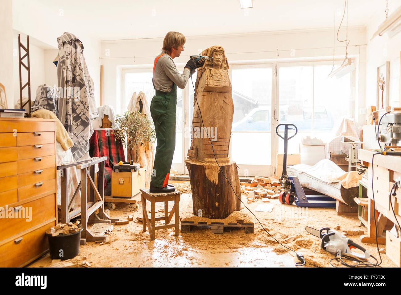 Intagliatore di legno in officina a lavorare sulla scultura con