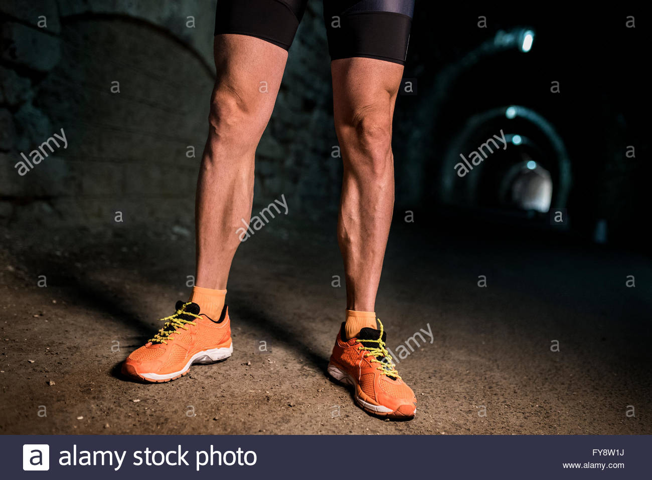 Muscolare di gambe di un corridore in un tunnel Immagini Stock