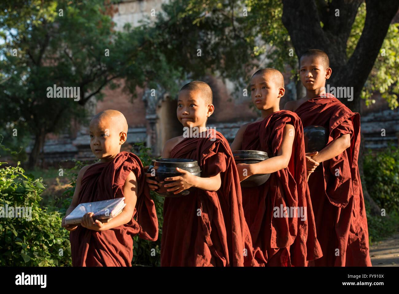 Myanmar, Amarapura, Monastero Mahagandayon, monaci buddisti con bocce raccogliere donazioni di cibo per il loro Immagini Stock