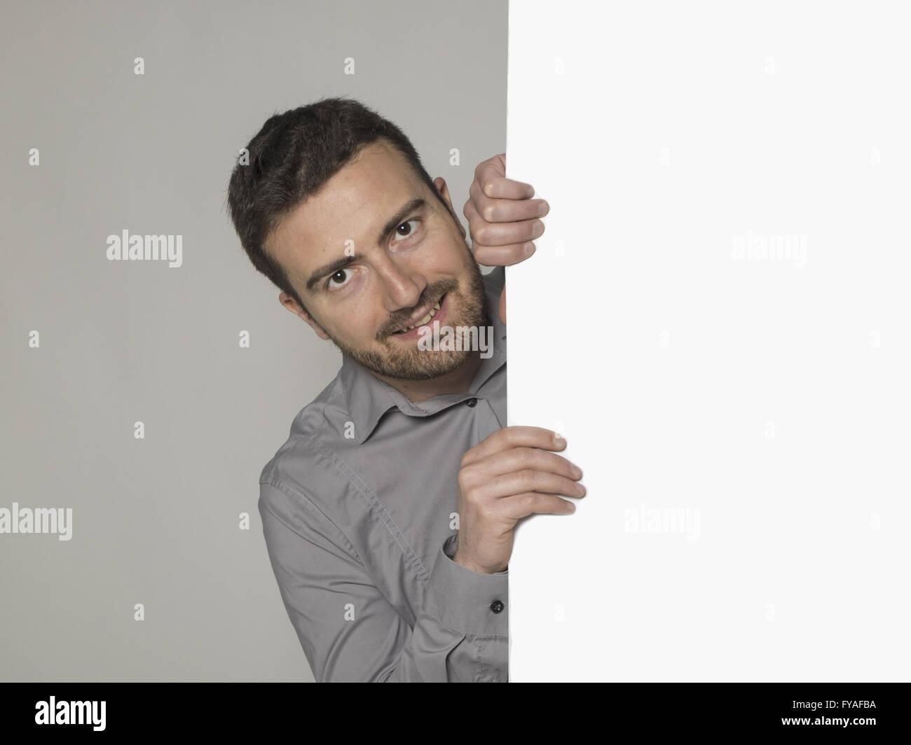 Uomo sorridente dietro un grande cartello Immagini Stock