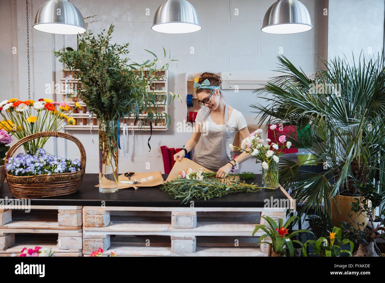 Allegro carino donna giovane fioraio godendo la creazione di bouquet in negozio di fiori Immagini Stock