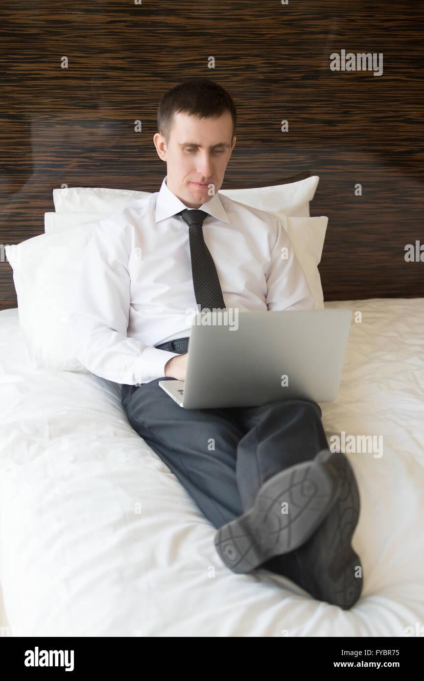 A piena lunghezza Ritratto di grave bel giovane uomo d affari in seduta formale di usura sui cuscini sul letto e Immagini Stock