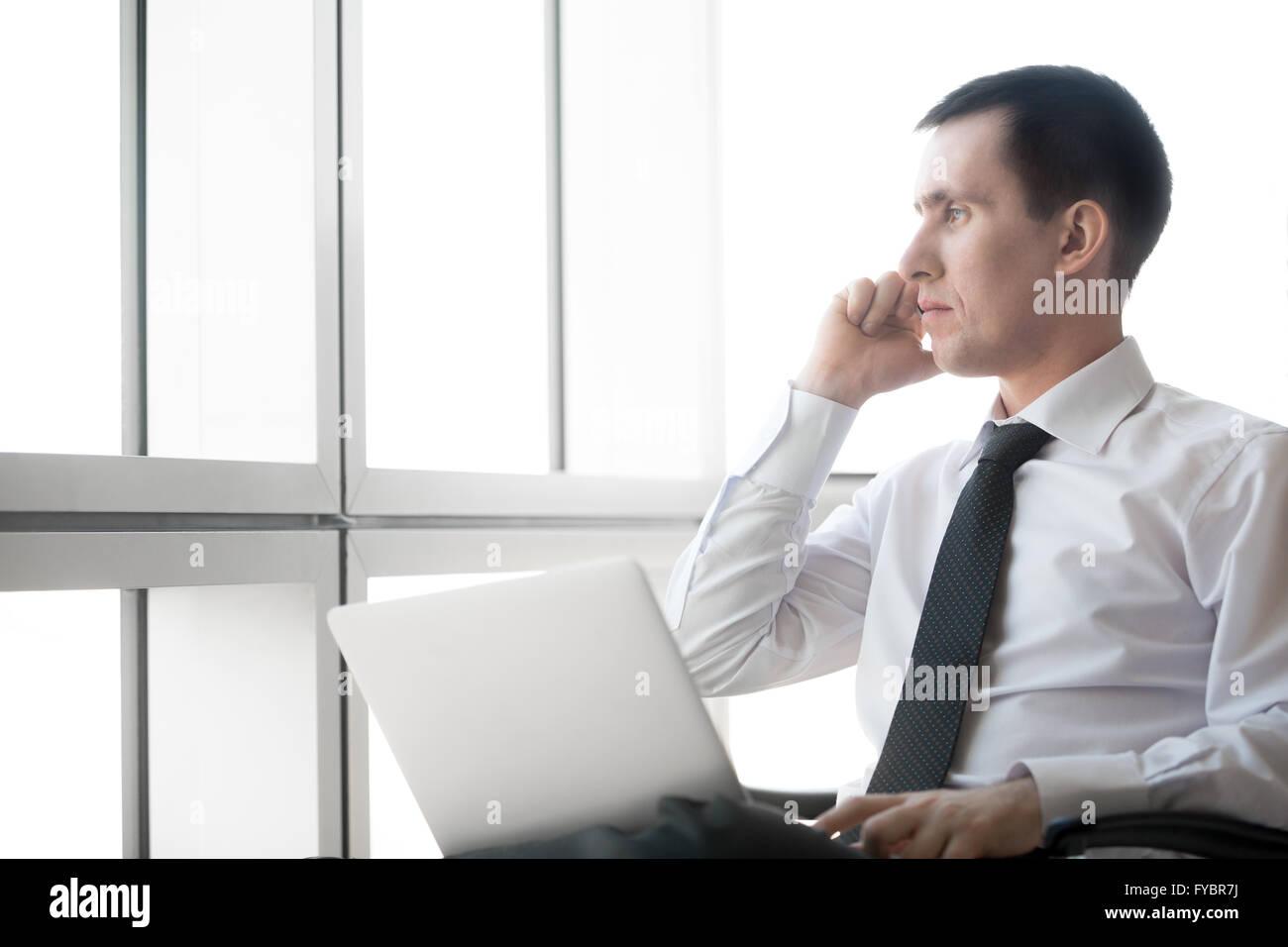 Ritratto di grave bel giovane uomo d affari lavorando sul computer portatile ed effettuare una chiamata. Imprenditore Immagini Stock