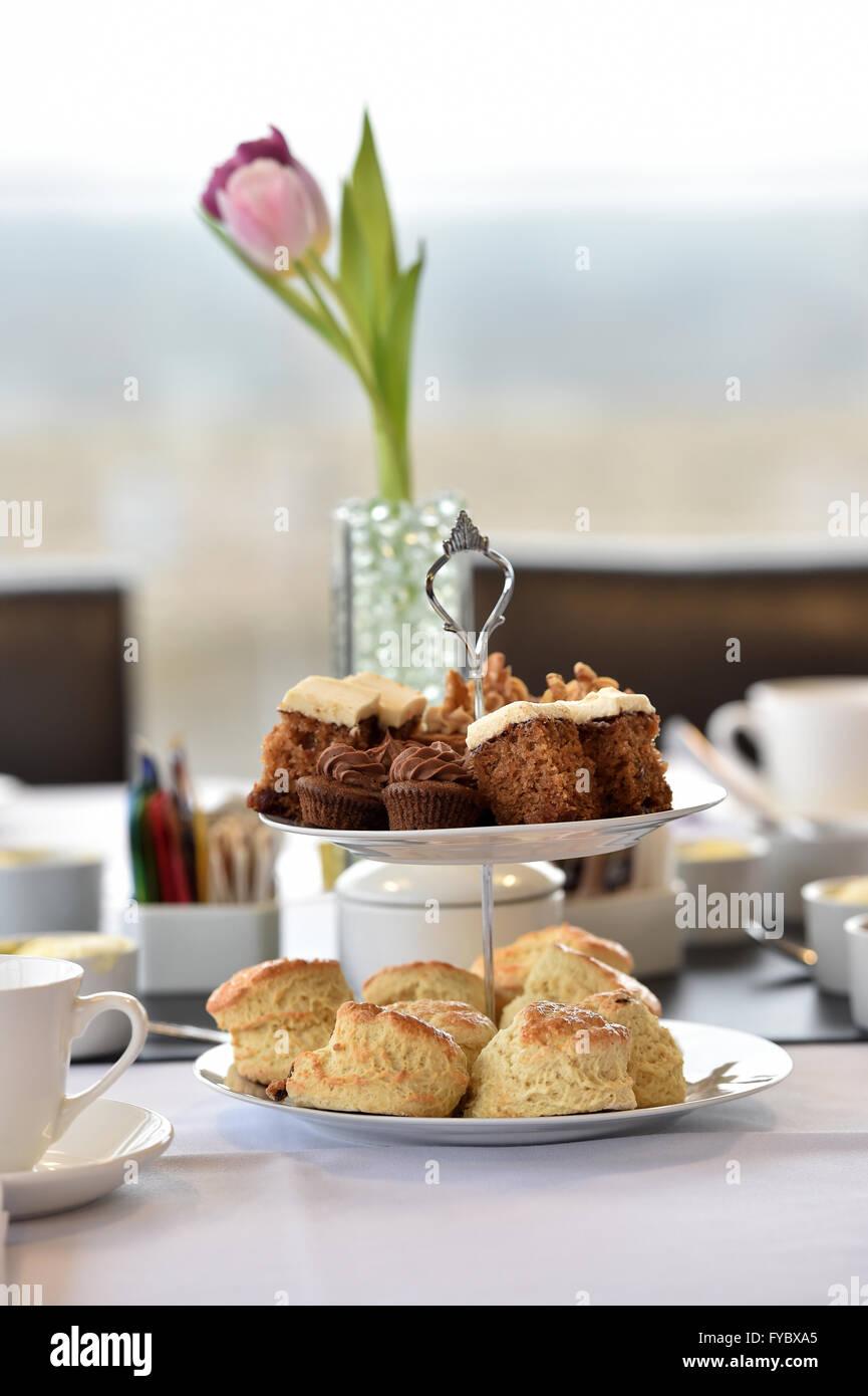 Il tè del pomeriggio in un ambiente di ufficio Cake Scones 2 tier cake stand Tulip fiori Immagini Stock