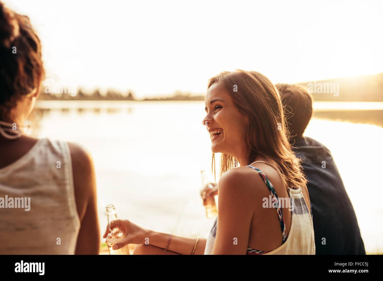 Ritratto di giovane sorridente ragazza seduta da un lago con i suoi amici. Giovani godendo una giornata al lago. Immagini Stock