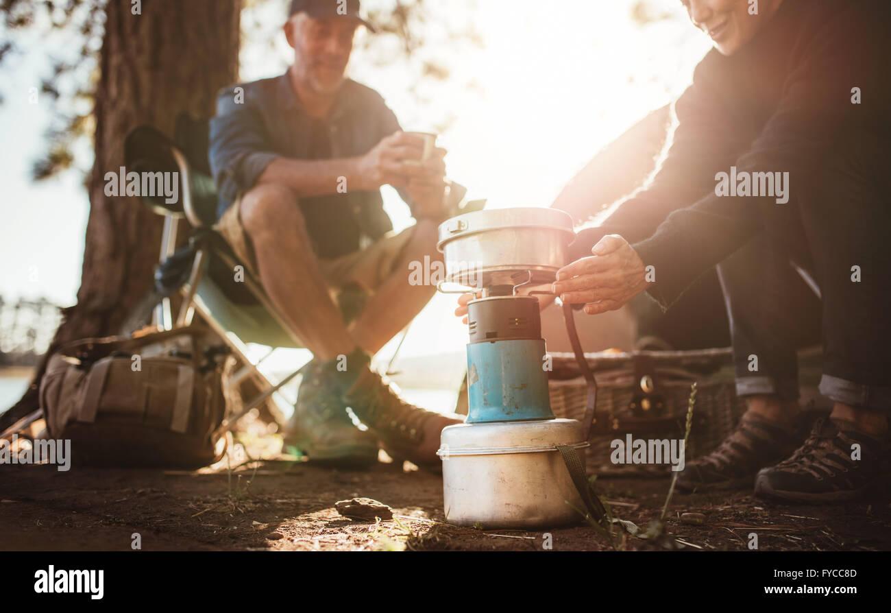Giovane seduto presso il campeggio in una giornata di sole, con la donna riscaldando le mani sulla stufa di camp. Immagini Stock