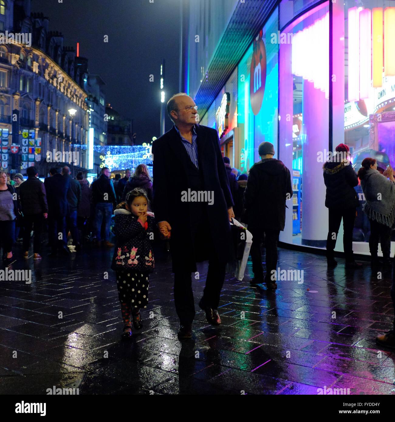L'uomo azienda giovane ragazza con la mano mentre camminando sul marciapiede umido di notte a Londra Foto Stock