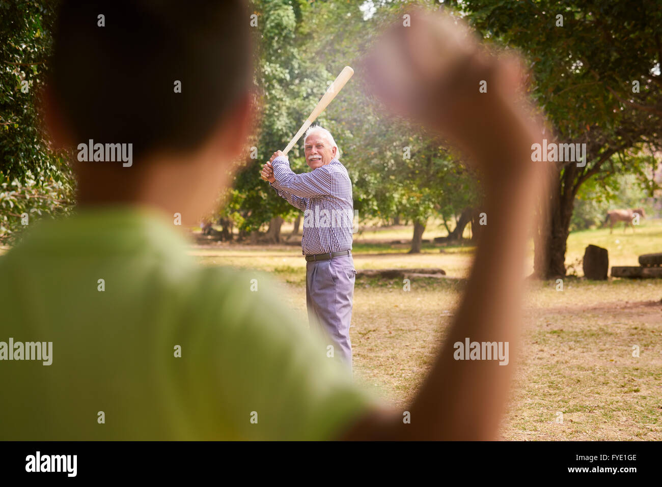 I nonni di trascorrere del tempo con il nipote: Senior uomo a giocare a baseball con il nipote nel parco. Il vecchio Immagini Stock