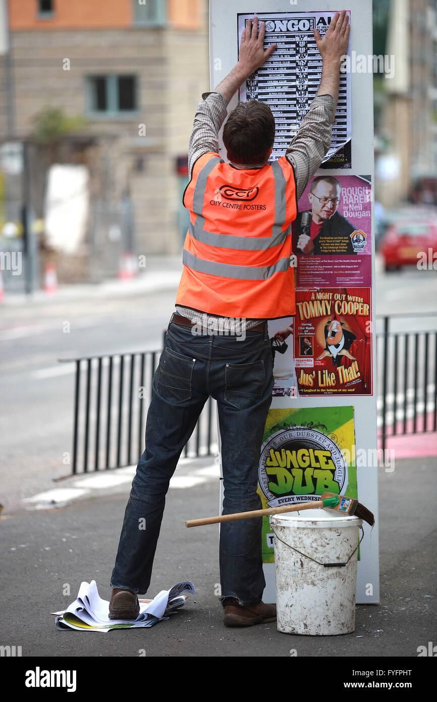 Un lavoratore di Festival di Edimburgo appeso un poster in Edinburgh Street come un Festival di Edimburgo promozione. Immagini Stock