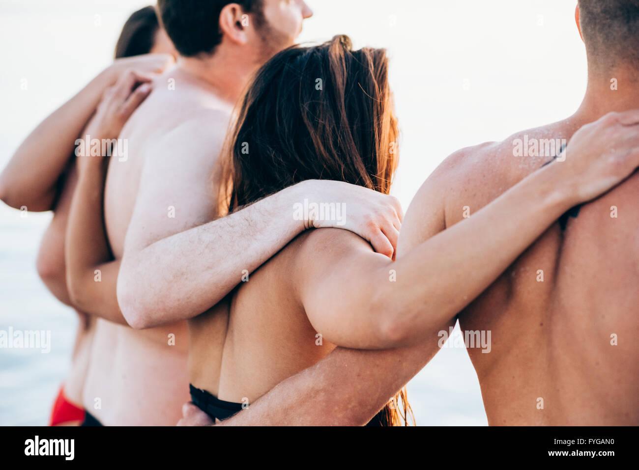 Vista posteriore di un gruppo di giovani amici multietnica di uomini e donne in spiaggia in estate abbracciando Immagini Stock