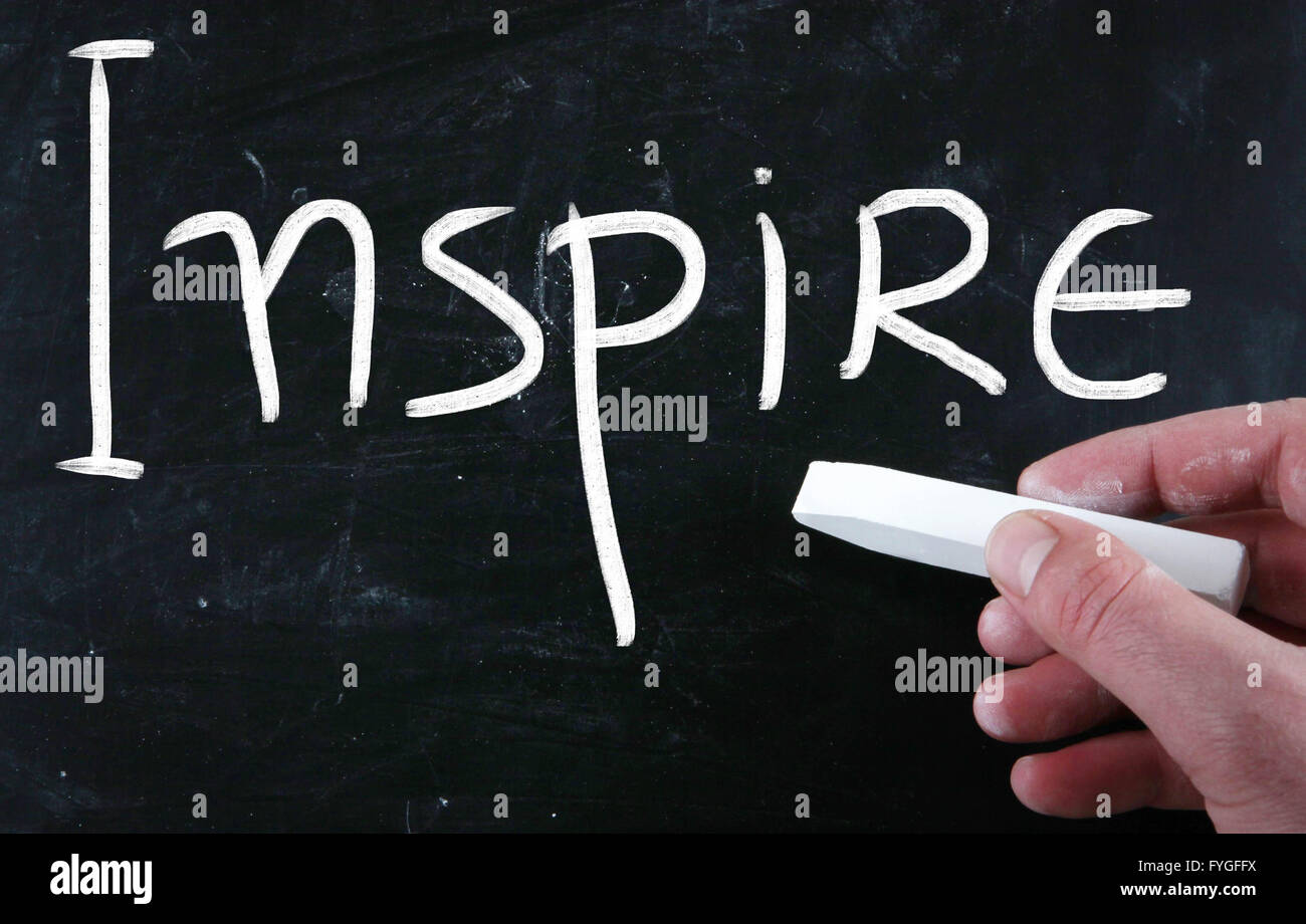 Ispirare scritta a mano con il bianco gesso su una lavagna Immagini Stock