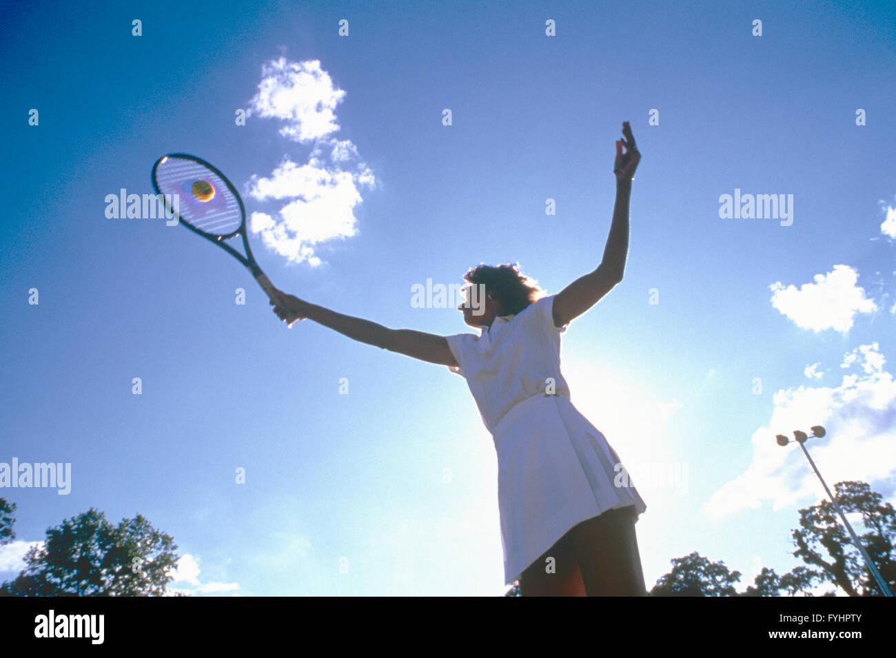 Femmina giocatore di tennis di colpire la palla con la racchetta Immagini Stock