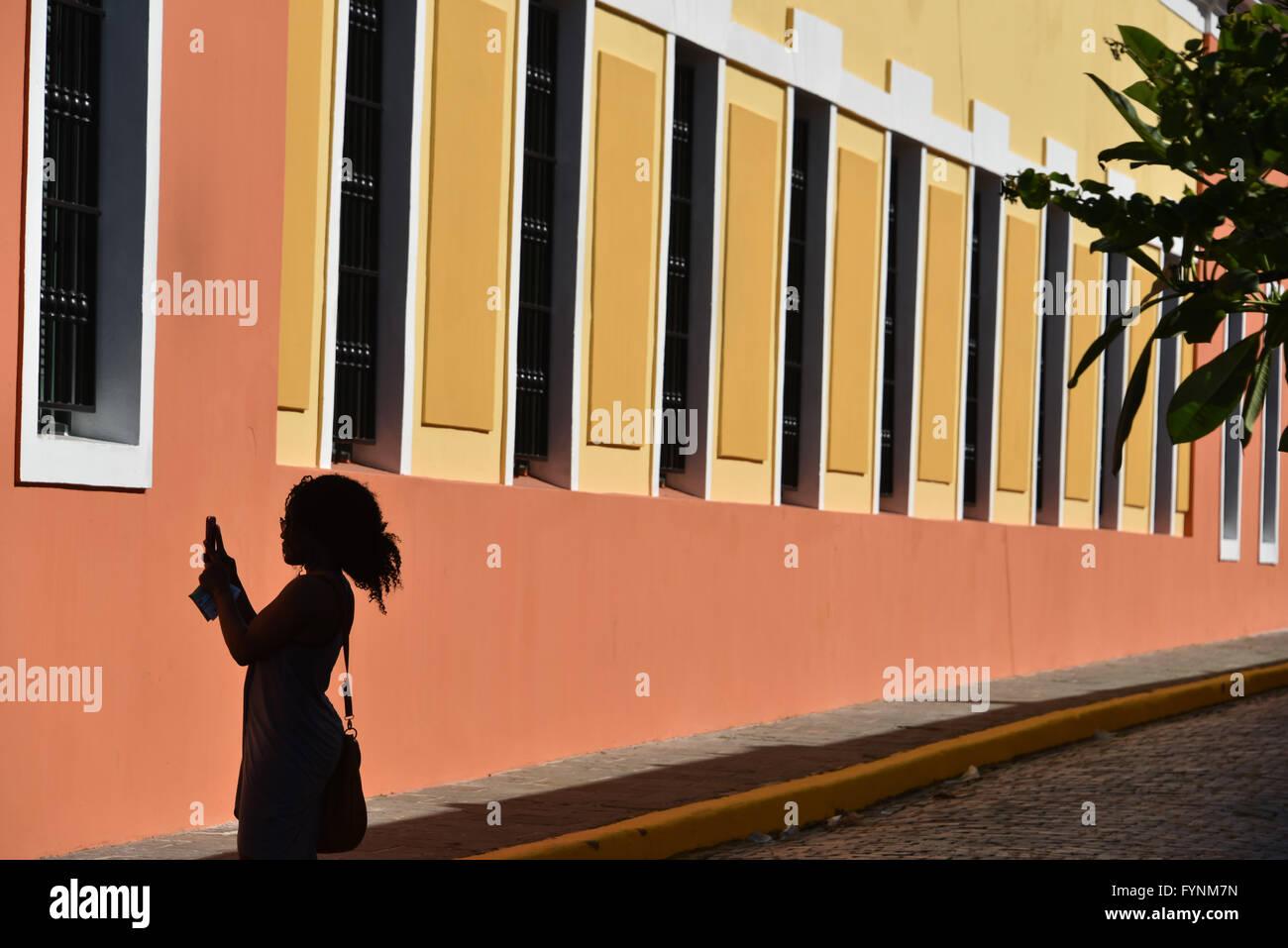 Silhouette di un turista di scattare una foto di edifici colorati nella vecchia San Juan, Puerto Rico Immagini Stock