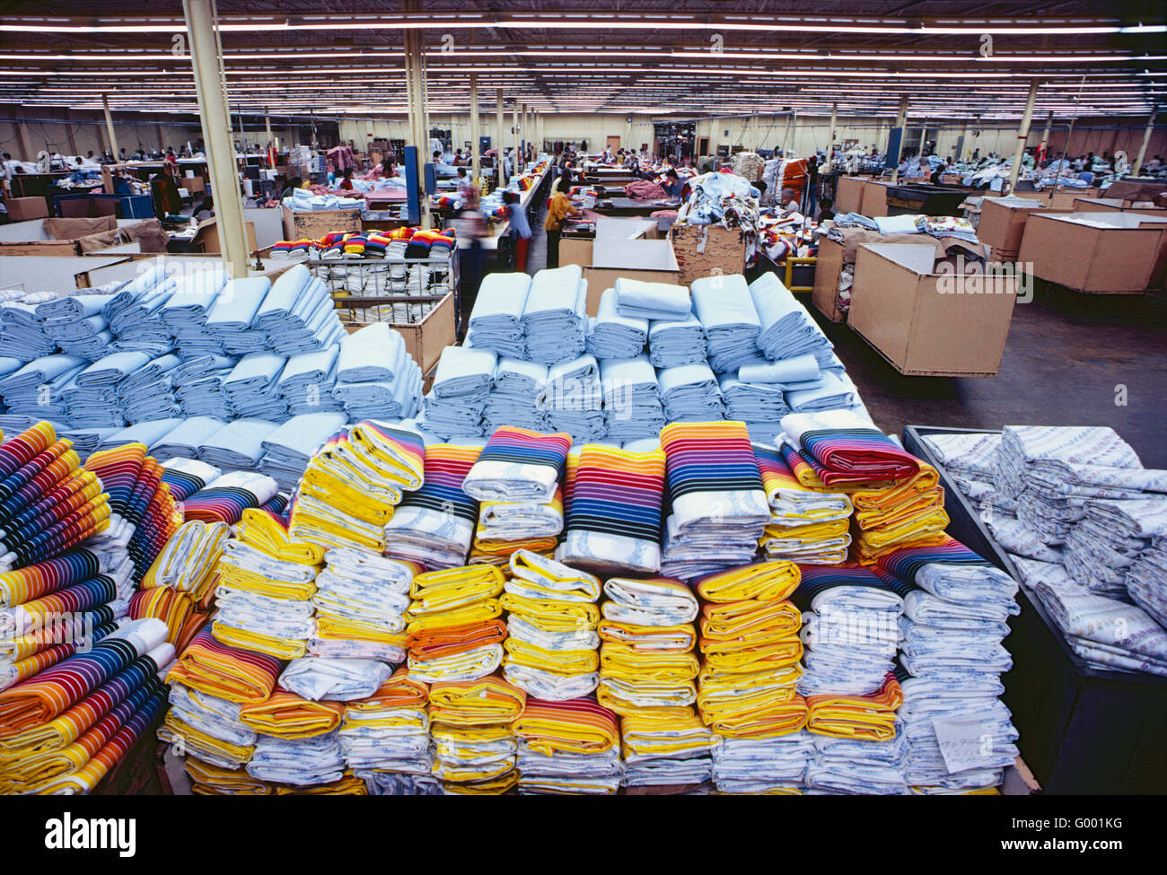 Pile di colorato finito di lenzuola di cotone in un indumento manufacturing facility Immagini Stock