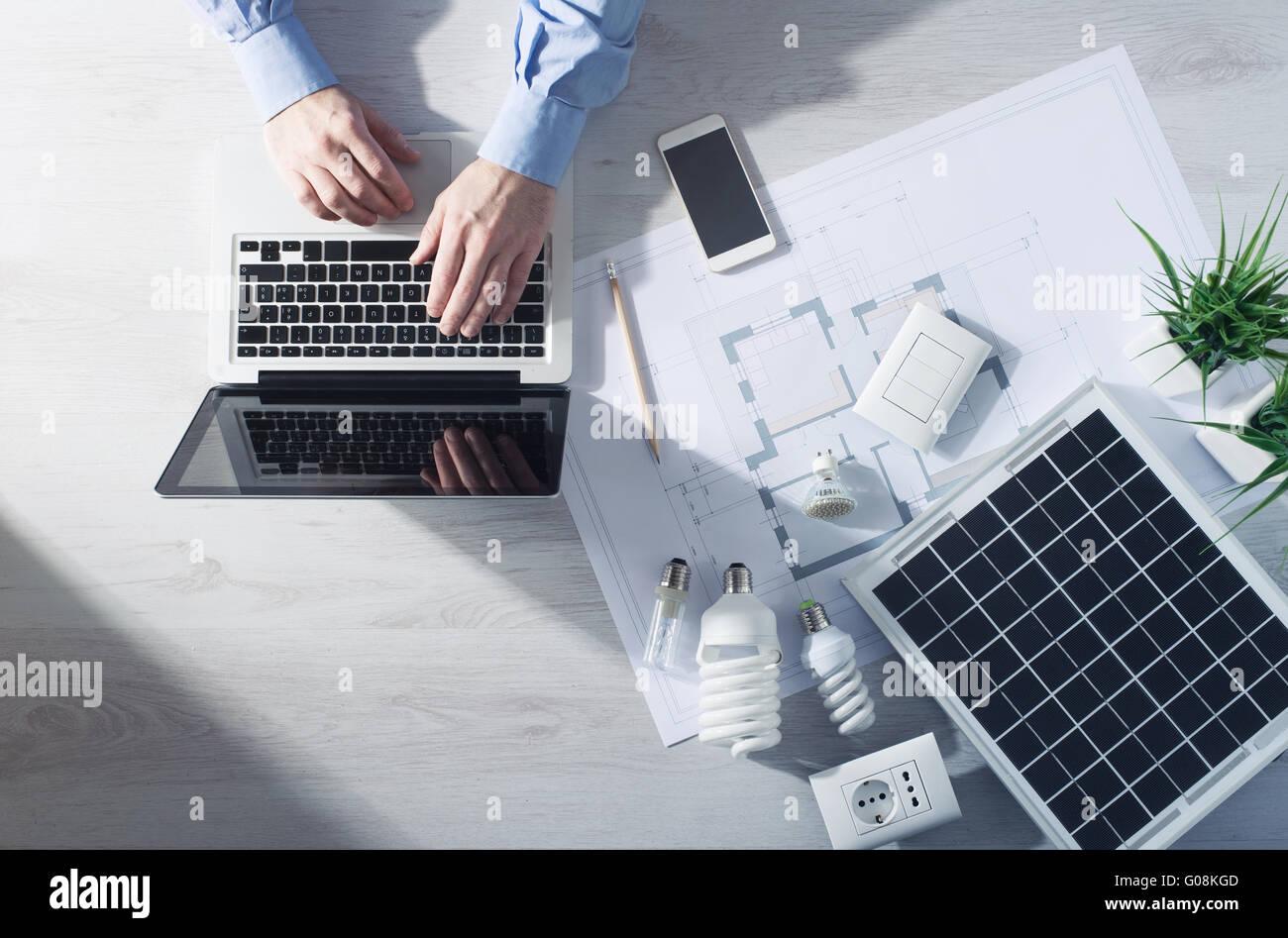 Uomo che lavora alla sua scrivania su un portatile con il risparmio energetico lampadine CFL, un pannello solare Immagini Stock