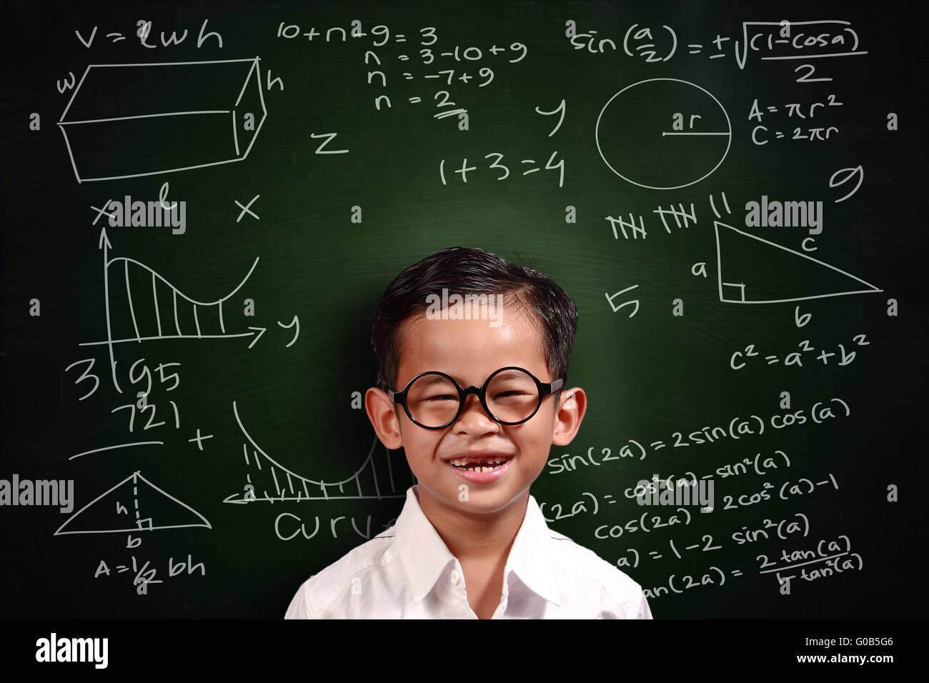 Little Genius studente asiatico ragazzo con gli occhiali sorridente su lavagna verde con math equivalenti scritto Immagini Stock