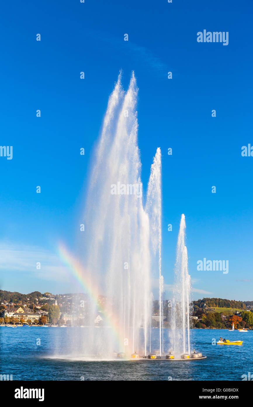 Splendida vista sulla fontana a Mythenquai con arcobaleno nel lago di Zurigo al tramonto, Svizzera Immagini Stock