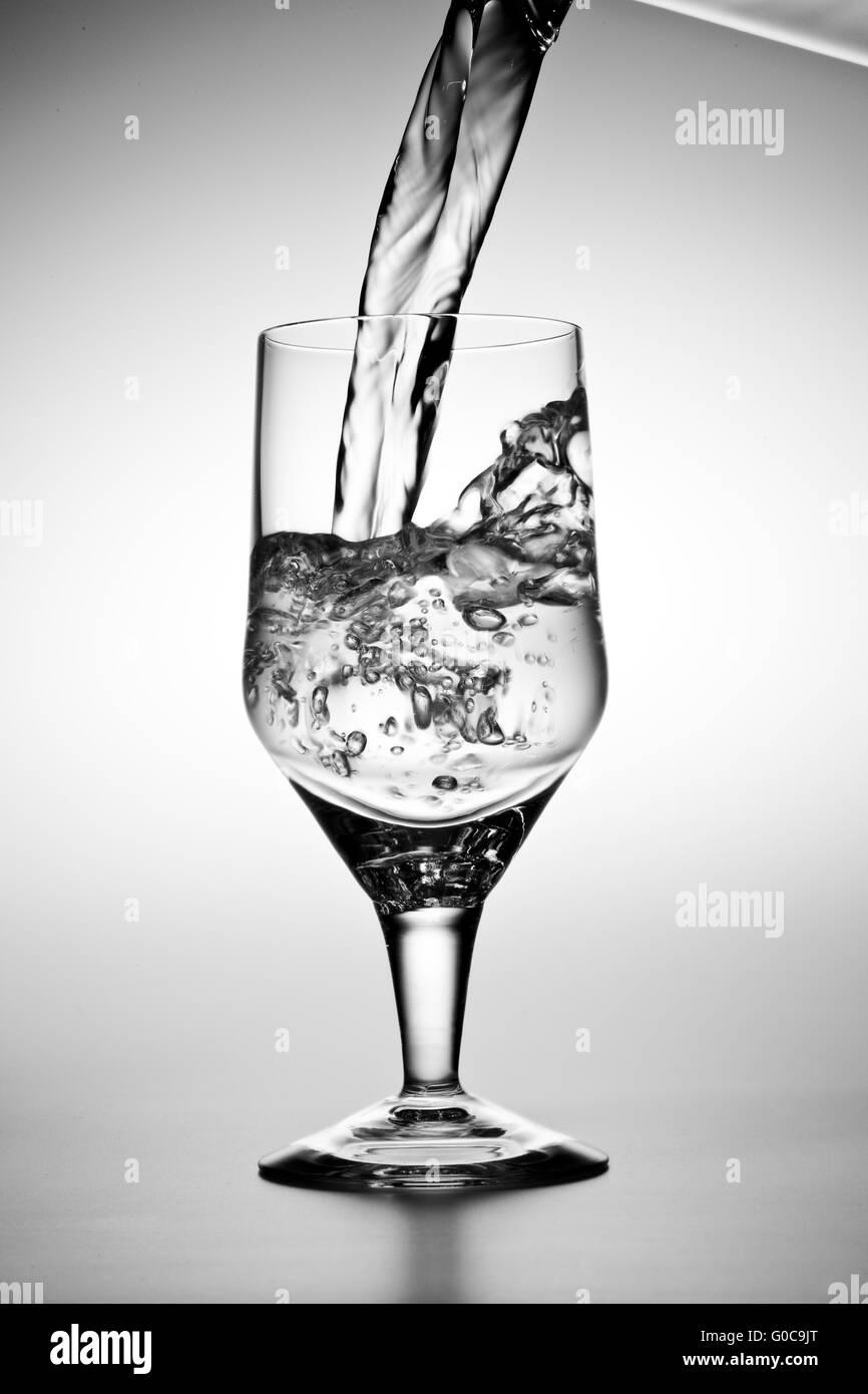 L'acqua viene versata in un bicchiere Immagini Stock