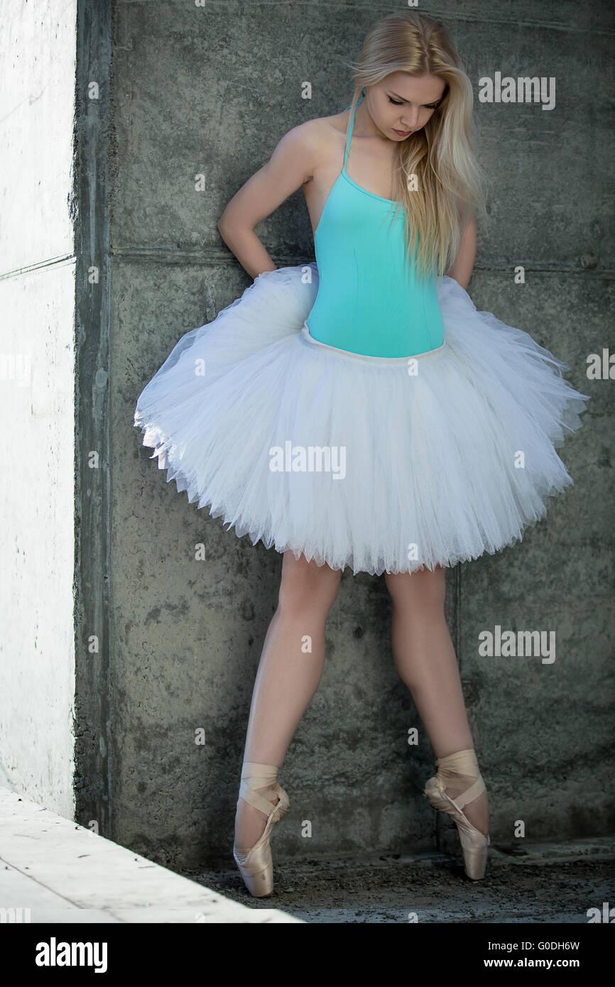 Leggiadra danzatrice con capelli biondi sullo sfondo di grigio concre Immagini Stock