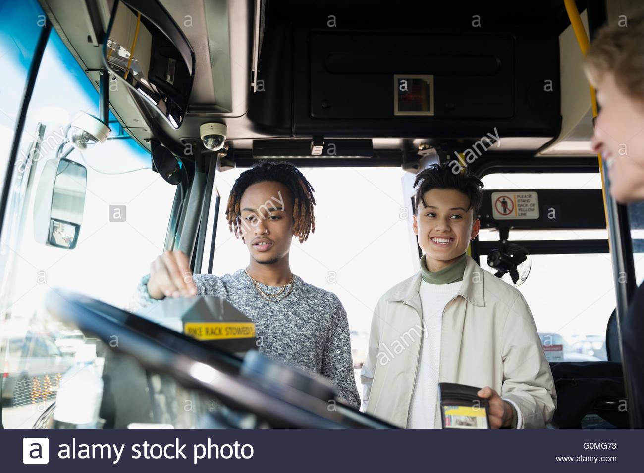 Giovani uomini di salire a bordo del bus ticket dando al conducente Immagini Stock