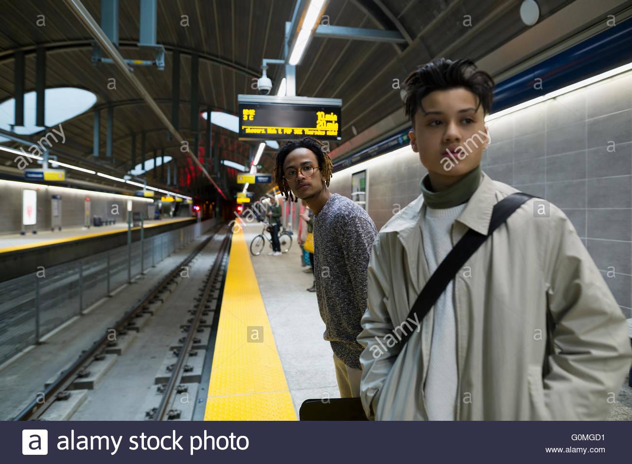 Giovani uomini in attesa sulla stazione della metropolitana platform Immagini Stock