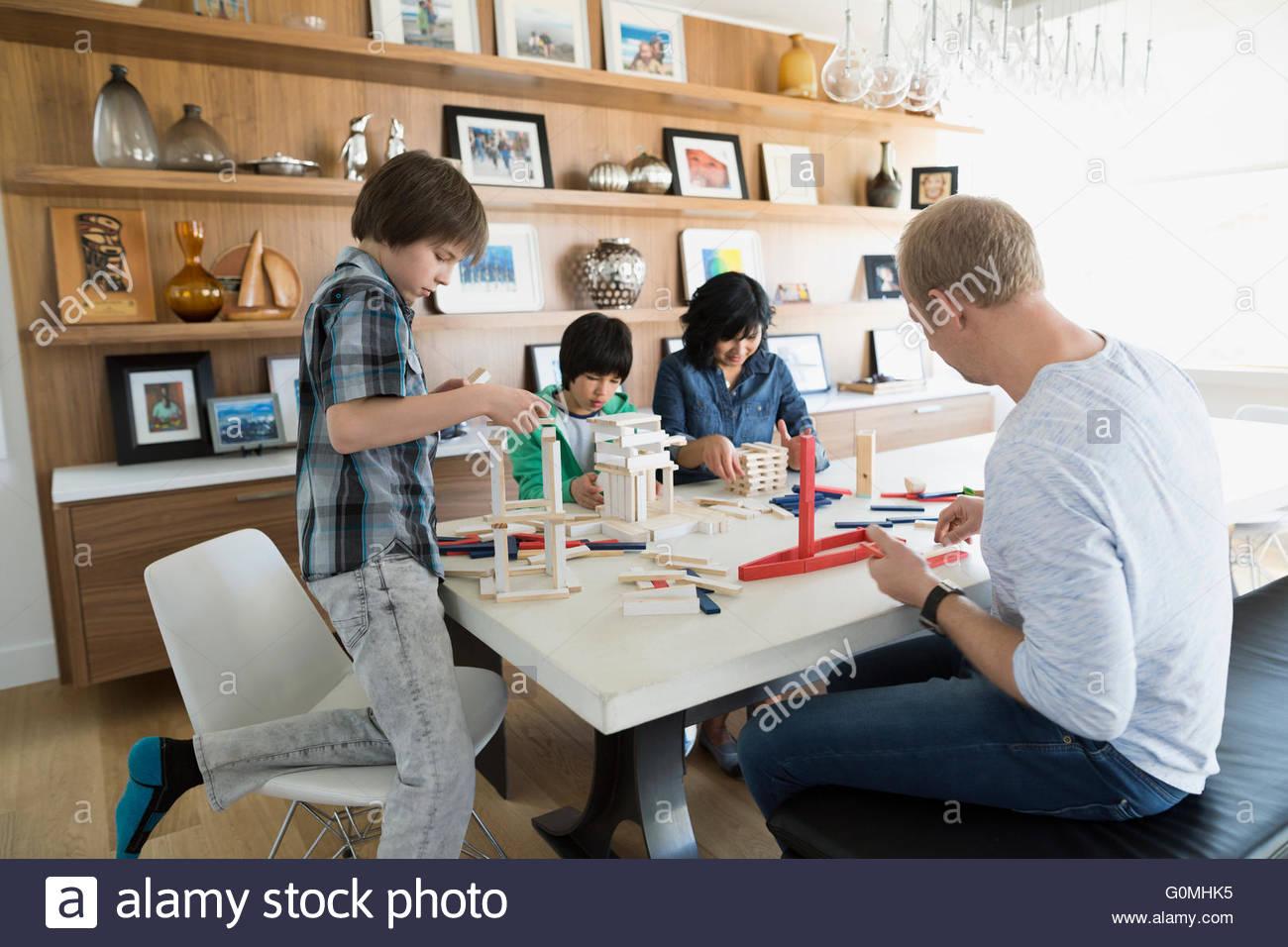 La famiglia gioca con la costruzione di orologi al tavolo da pranzo Immagini Stock
