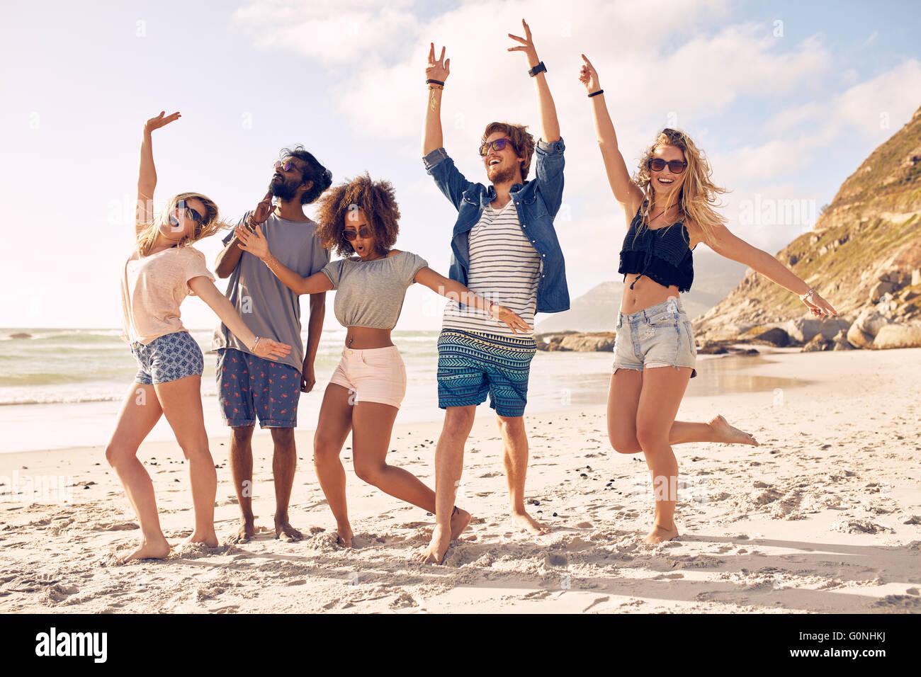 Ritratto di entusiasti giovani amici permanente sulla spiaggia. Gruppo multirazziale di amici godendo una giornata Immagini Stock