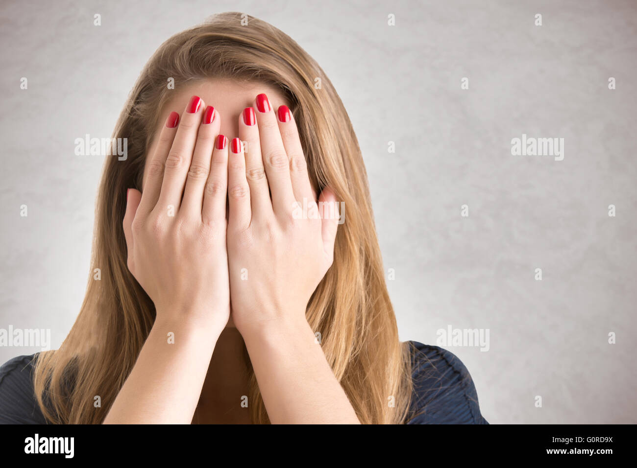 Ragazza timida per coprire il suo volto con le sue mani, isolato Immagini Stock